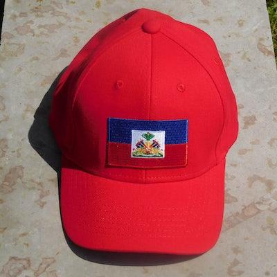 Rode pet met vlag Haiti en HAITI in goud op de achterkant
